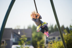 A young girl smiling on her swing that is in mid-air